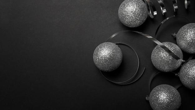 Enfeites de natal cinza na mesa preta