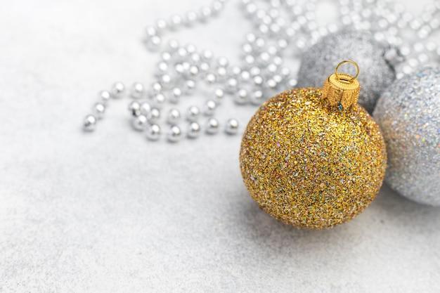 Enfeites de natal com bola de ouro e prata em plano de fundo texturizado desfocado com espaço para texto, ano novo