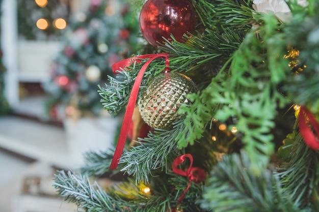 Enfeites de natal com fita cacheada na árvore do abeto. ramos da linda árvore de natal com brinquedos dourados, brancos e vermelhos. decorações de ano novo. fundo de brilho e fada. feliz natal e feliz ano novo
