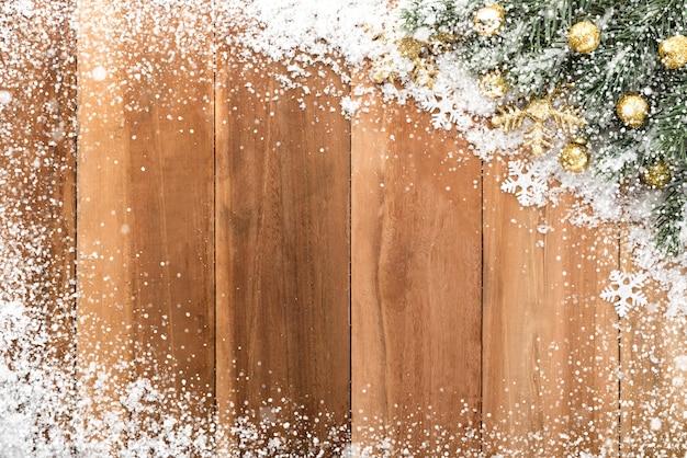 Enfeites de natal com neve no fundo de madeira