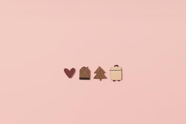 Enfeites de natal de madeira e símbolos de uma época festiva de férias. árvore de natal, coração vermelho, mala e uma casa de mini brinquedos plana leigos com espaço de cópia em um fundo rosa pastel.