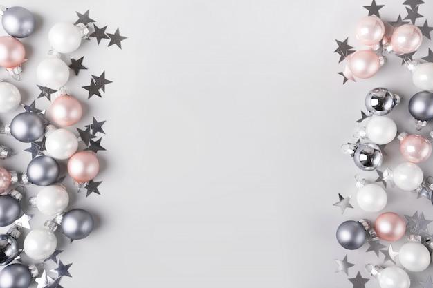 Enfeites de natal-de-rosa e prata, estrelas de confete como quadro em fundo cinza pastel. vista superior com espaço para texto. postura plana.