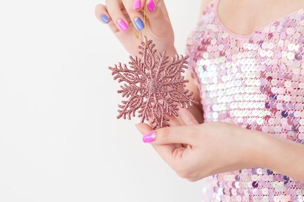 Enfeites de natal e decoração festiva. ornamento do feriado de ano novo. mulher segurando um floco de neve brilhante de ouro rosa