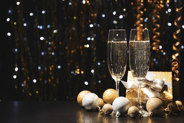 Enfeites de natal e taças de champanhe no espaço borrado, copie o espaço