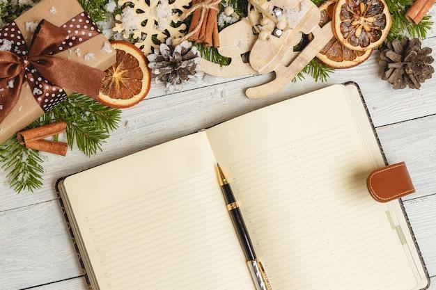 Enfeites de natal e um caderno em branco aberto sobre uma mesa de madeira clara