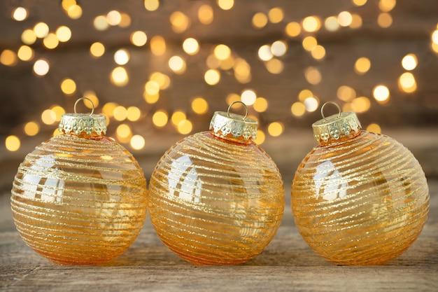 Enfeites de natal em fundo de madeira com luzes desfocadas