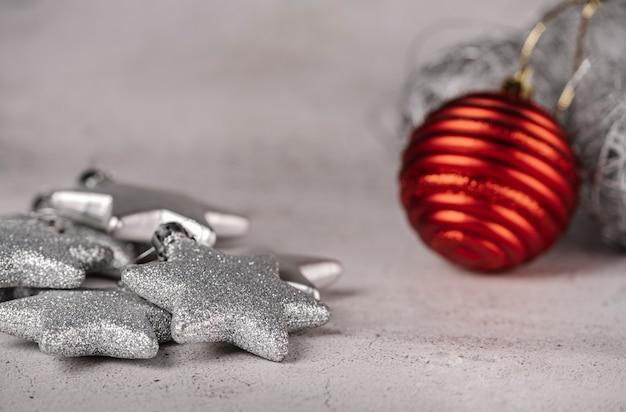 Enfeites de natal em um fundo cinza, estrelas de prata com glitter