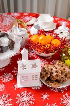 Enfeites de natal na mesa com biscoitos cítricos e rosa mosqueta na mesa festiva