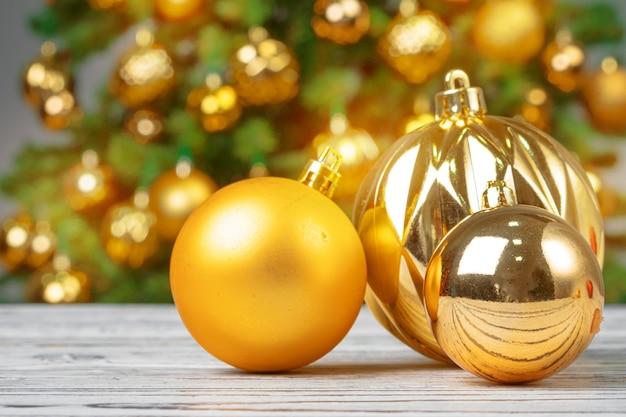 Enfeites de natal na mesa de madeira contra a árvore de natal decorada turva