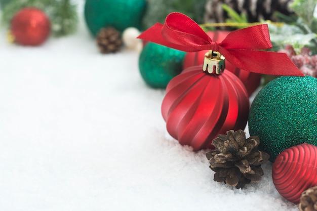 Enfeites de natal vermelho com ramos de abeto, pinhas, na neve branca.
