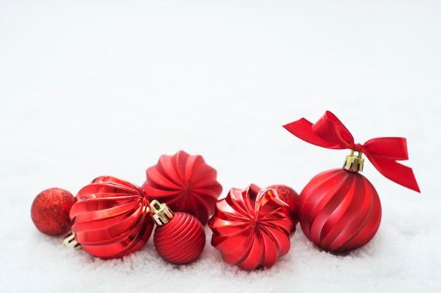 Enfeites de natal vermelho isolados na neve. cartão de inverno. copie o espaço.