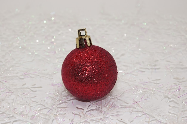 Enfeites de natal vermelhos brilhantes redondos em uma mesa com flocos de neve