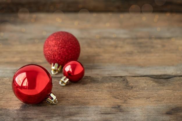 Enfeites de natal vermelhos em fundo de madeira
