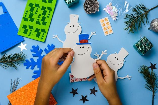Enfeites de suspensão de árvore de natal. peças de boneco de neve em fundo azul de madeira. ideias de artesanato de natal. vista do topo. fechar-se. faça você mesmo.