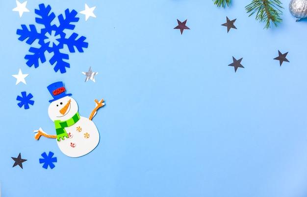 Enfeites de suspensão de árvore de natal. peças de boneco de neve em fundo azul.