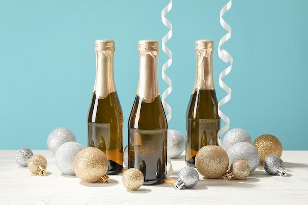 Enfeites e mini garrafas de champanhe contra o espaço azul, espaço para texto