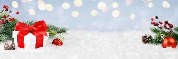 Enfeites festivos de decoração de natal na paisagem de inverno com caixa de presente e enfeites