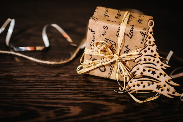 Enfeites para árvores de natal e um presente, caixa com fitas em uma mesa de madeira estrutural marrom. vista lateral, local para texto.