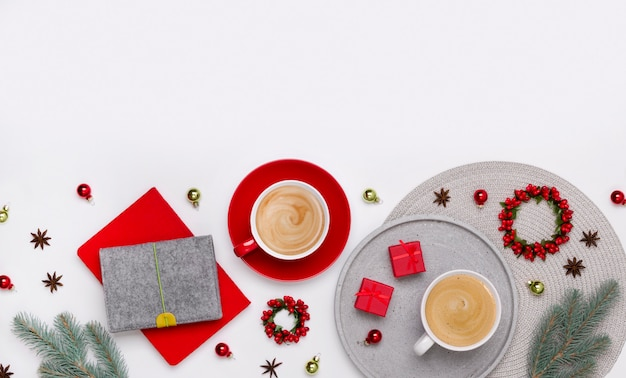 Enfeites, ramos de abeto, duas xícaras de café e caixas de presente vermelhas