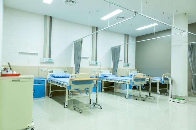 Enfermaria de hospital com leitos e equipamentos médicos.