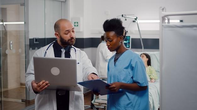 Enfermeira africana e médico cirurgião em uniforme médico analisando sintoma de doença trabalhando em enfermaria de hospital