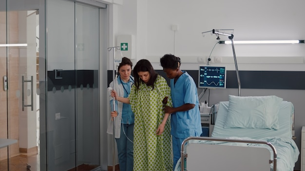 Enfermeira afro-americana com médico ajudando paciente a se levantar da cama