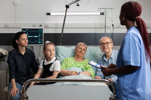 Enfermeira afro-americana discutindo sintomas de doença com uma mulher idosa e doente