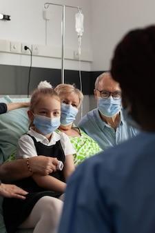 Enfermeira afro-americana monitorando idosa idosa após cirurgia clínica