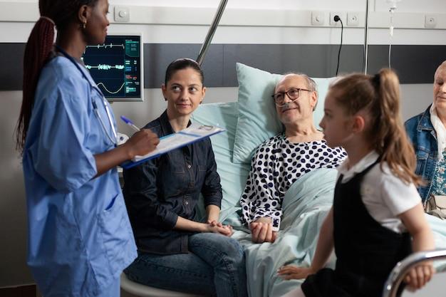 Enfermeira afro-americana monitorando paciente idoso doente escrevendo experiência sobre doença