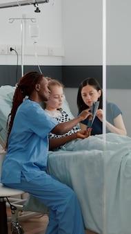 Enfermeira afro-americana mostrando radiografia de pulmão explicando sintomas de doenças respiratórias