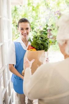 Enfermeira agradável trazer legumes ao paciente idoso em casa