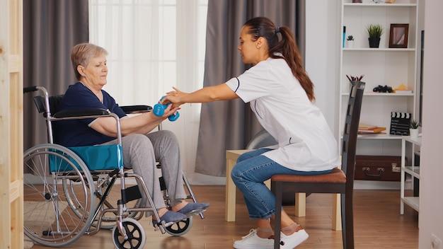 Enfermeira ajudando mulher idosa em cadeira de rodas com reabilitação. treinamento, esporte, recuperação e levantamento de peso, lar de terceira idade, enfermagem de saúde, apoio à saúde, assistência social, médico e domicílio