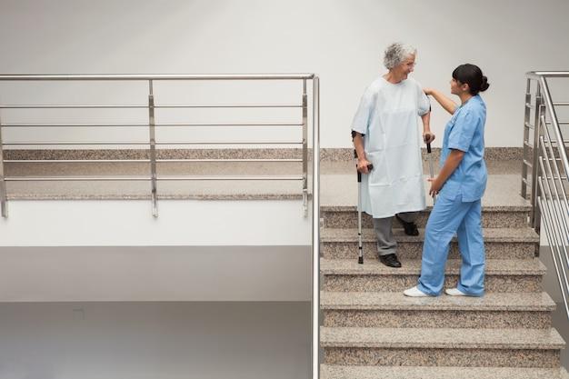 Enfermeira ajudando senhora idosa a descer as escadas