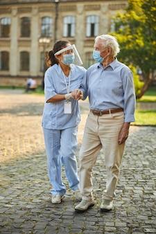 Enfermeira ajudando um homem idoso enquanto caminhava ao ar livre