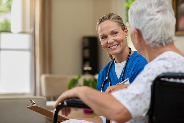 Enfermeira amigável falando com paciente sênior