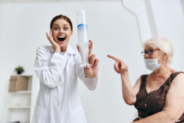Enfermeira aplicando injeção em uma senhora idosa no braço de um hospital