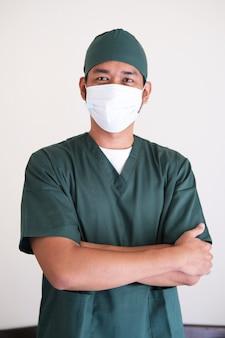 Enfermeira asiática em pé com as mãos cruzadas no peito