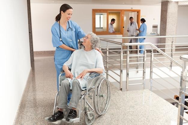 Enfermeira assistindo velhas mulheres sentadas em cadeira de rodas