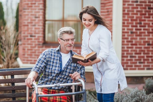 Enfermeira bonita lendo um livro para velho perto de hispital