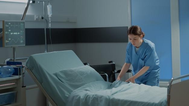 Enfermeira caucasiana fazendo a cama da enfermaria do hospital para usar