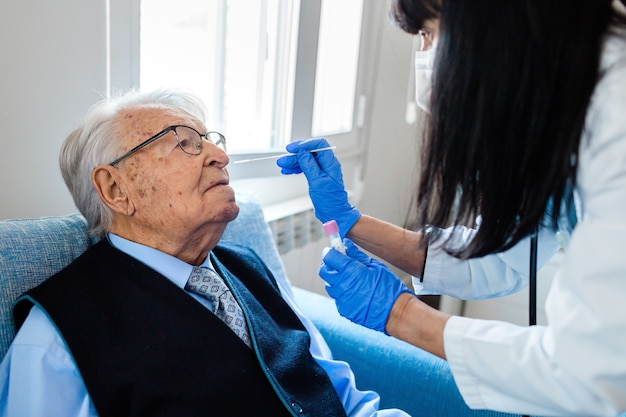 Enfermeira com luvas higiênicas azuis, realizando teste cobiçoso em um homem idoso de camisa azul e gravata, sentado no sofá em casa. cuidados de saúde ao domicílio.