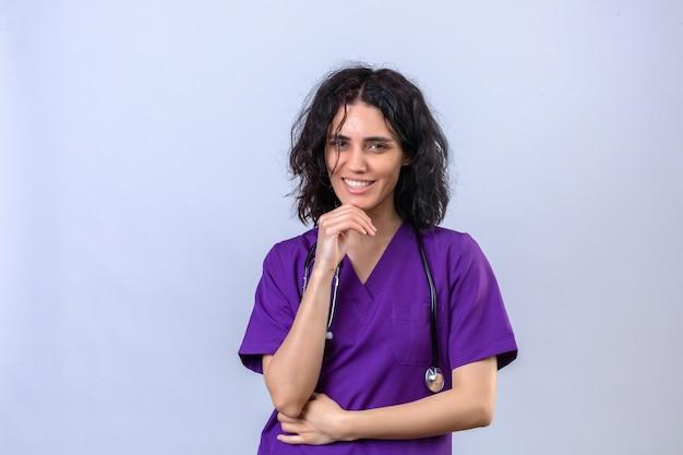 Enfermeira com uniforme médico e estetoscópio com a mão no queixo sorrindo confiante em pé no branco isolado