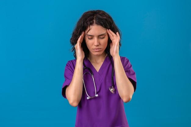 Enfermeira com uniforme médico e estetoscópio sentindo cansaço, tocando as têmporas, tendo dor de cabeça em pé no azul isolado