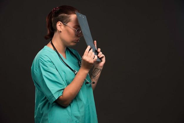 Enfermeira com uniforme verde faz anotações.