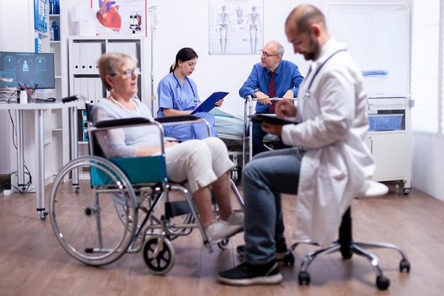 Enfermeira conversando com homem deficiente em quarto de hospital durante consulta