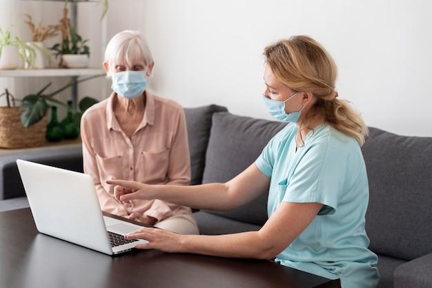 Enfermeira conversando com uma mulher mais velha na casa de saúde