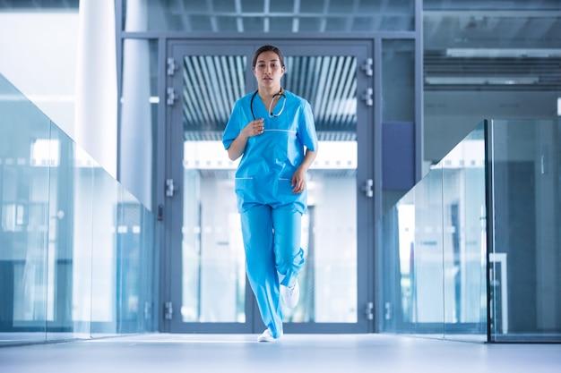 Enfermeira correndo no corredor do hospital