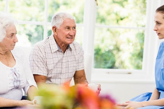 Enfermeira cuidando de pacientes idosos doentes em casa