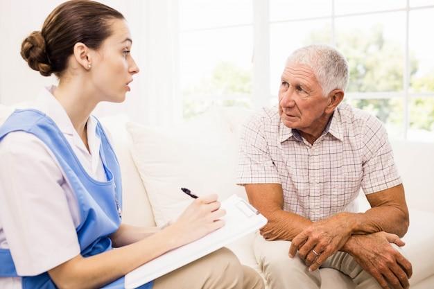 Enfermeira cuidando do paciente idoso doente em casa