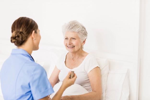 Enfermeira cuidando do sofrimento paciente sênior em casa